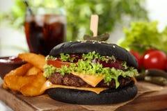 Hamburger et pommes frites noirs juteux sur le conseil en bois images stock