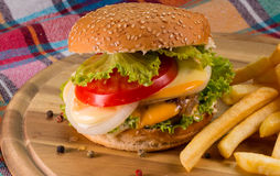 Hamburger et pommes frites sur la table en bois Photos stock