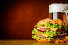 Hamburger et tasse de bière froide avec l'espace de copie Photos stock
