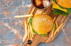 Hamburger fait à la maison grillé savoureux avec du boeuf, la tomate, le fromage, le concombre, les pommes frites et la laitue su photos libres de droits