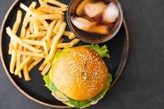 Hamburger fait à la maison grillé savoureux avec du boeuf, la tomate, le fromage, le concombre, les pommes frites et la laitue su photo stock