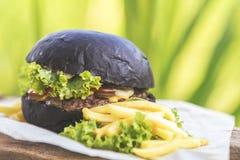 Hamburger fait avec le petit pain noir de charbon de bois servi Images libres de droits