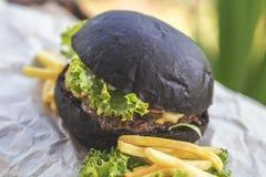 Hamburger fait avec le petit pain noir de charbon de bois servi Photo libre de droits