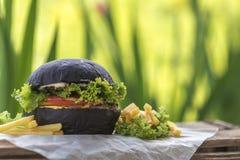 Hamburger fait avec le petit pain noir de charbon de bois servi Photos libres de droits