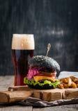 Hamburger fait maison avec le petit pain noir Photos stock