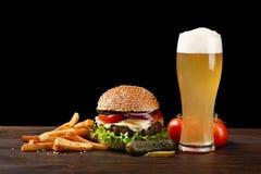 Hamburger fait maison avec les pommes frites et le verre de bière sur la table en bois Prêt-à-manger sur le fond foncé photo libre de droits