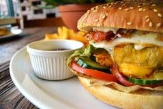 Hamburger fait maison de lard avec du fromage et des légumes d'oeufs images stock