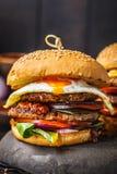 Hamburger fait maison de viande avec l'oeuf, la sauce et les légumes sur le fond foncé photo stock