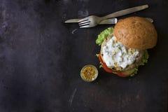 Hamburger fait maison frais avec de la sauce, les cornichons et les herbes épicés au-dessus du fond foncé en métal photos stock