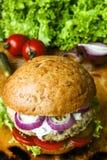 Hamburger fait maison frais avec de la sauce, les cornichons et les herbes épicés au-dessus du fond foncé en métal photos libres de droits