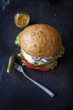 Hamburger fait maison frais avec de la sauce, les cornichons et les herbes épicés au-dessus du fond foncé en métal image libre de droits