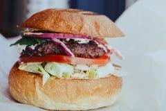 Hamburger fait maison frais d?licieux de fromage avec les anneaux grill?s de viande, de fromage, de tomates, de laitue et d'oigno photo libre de droits