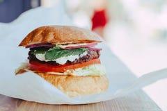 Hamburger fait maison frais d?licieux de fromage avec les anneaux grill?s de viande, de fromage, de tomates, de laitue et d'oigno photographie stock libre de droits