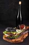 Hamburger fait maison frais sur le panneau en bois de portion avec la sauce tomate de fourchette et de couteau et la bouteille de Photo libre de droits