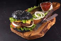 Hamburger fait maison frais sur le panneau en bois de portion avec la sauce tomate de fourchette et de couteau sur le fond foncé Image stock