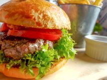 Hamburger Fast Food. Hamburger with cutlet grilled on a wooden plate andfrench fries in the background royalty free stock photography