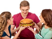 Hamburger fast food in people friends hands. Hamburger fast food with ham in people hands. Fast food concept. Friends men and two women eating sandwich junk in Stock Images