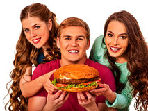 Hamburger fast food in people friends hands . Stock Photos