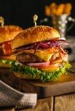 Hamburger frais délicieux avec de la viande, le lard, le fromage et les légumes o Photographie stock