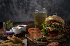 Hamburger frais et juteux Hamburger de fromage avec du boeuf ou lard, tomate de petit pâté, anneau d'oignon et eau ou bière de sc photo stock