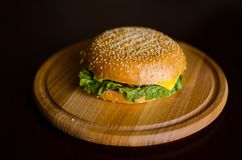 Hamburger frais juteux sur un conseil en bois photos stock