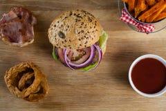 Hamburger, francuscy dłoniaki, cebulkowy pierścionek i pomidorowy kumberland na ciapanie desce, zdjęcia royalty free