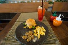 Hamburger, francuscy dłoniaki, kurczak Kara Kay na czarnym talerzu Fotografia Stock