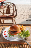 Hamburger and french fries in beach cafe Stock Images