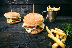 Hamburger with french fries, beer on a burnt, black wooden table. Fast food meal. Homemade hamburger consist of beef meat, lettuce Stock Photo