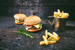 Hamburger with french fries, beer on a burnt, black wooden table. Fast food meal. Homemade hamburger consist of beef meat, lettuce Stock Image