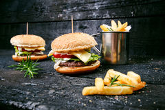 Hamburger with french fries, beer on a burnt, black wooden table. Fast food meal. Homemade hamburger consist of beef meat, lettuce Stock Images