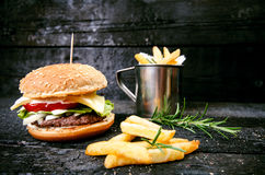 Hamburger with french fries, beer on a burnt, black wooden table. Fast food meal. Homemade hamburger consist of beef meat, lettuce Stock Photos