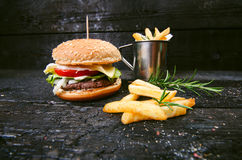 Hamburger with french fries, beer on a burnt, black wooden table. Fast food meal. Homemade hamburger consist of beef meat, lettuce Royalty Free Stock Photo