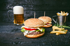 Hamburger with french fries, beer on a burnt, black wooden table. Fast food meal. Homemade hamburger consist of beef meat, lettuce Royalty Free Stock Photos