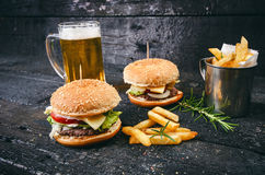 Hamburger with french fries, beer on a burnt, black wooden table. Fast food meal. Homemade hamburger consist of beef meat, lettuce. Tomato, bins, dressing Royalty Free Stock Photography