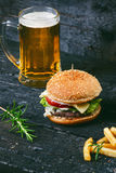 Hamburger with french fries, beer on a burnt, black wooden table. Fast food meal. Homemade hamburger consist of beef meat, lettuce Royalty Free Stock Images