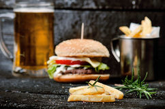 Hamburger with french fries, beer on a burnt, black wooden table. Fast food meal. Homemade hamburger consist of beef meat, lettuce Royalty Free Stock Image