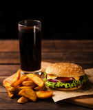 Hamburger, french fries and cola drink. On a dark wooden background Stock Photo
