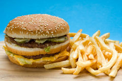 Hamburger and French Fries. On a cutboard against blue background Stock Photo