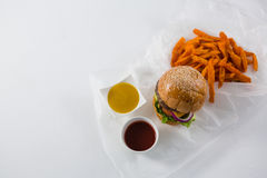 Hamburger by French fries and dips in bowl Royalty Free Stock Image