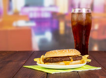 Hamburger with french fries, glass  cola on  background  hall cafe. Hamburger with french fries and a glass of cola on the background of the hall cafe Royalty Free Stock Image