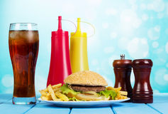 Hamburger, french fries, glass cola, sauces and spices on abstract. Stock Photos