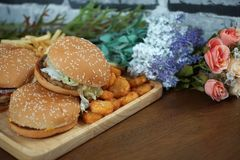 Hamburger with french fries ketchup and fresh vegetables on wooden board stock image