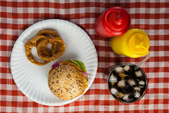 Hamburger, french fries, onion ring and cold drink on napkin Stock Photo