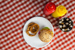 Hamburger, french fries, onion ring and cold drink on napkin Royalty Free Stock Image