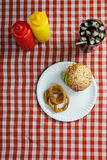 Hamburger, french fries, onion ring and cold drink on napkin Royalty Free Stock Images