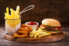 Hamburger with french fries and onion rings. On wooden board Royalty Free Stock Photo