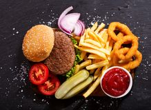 Hamburger with french fries and onion rings, top view. Hamburger with french fries and onion rings on wooden board, top view Stock Images