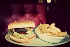 Hamburger and french fries plate in american food restaurant. Tasty hamburger and french fries on plate in american food restaurant. Red leather sofa in the Royalty Free Stock Image