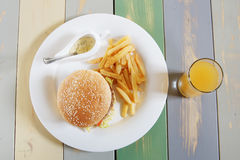 Hamburger with french fries and sauce on the wooden table Royalty Free Stock Image